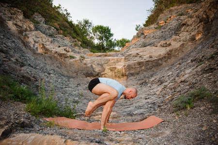 Young man doing an ashtavakrasana. Hand standing variant
