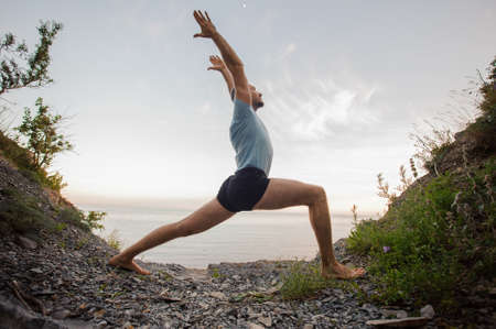 bold man doing yoga on the stone nearby ocean
