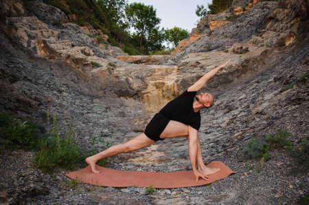 ser humano: Hombre que hace yoga al aire libre. Parshvakonasana. Vista lateral