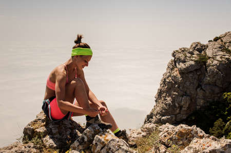 Young fitness woman trail runner tying shoelace at mountain top