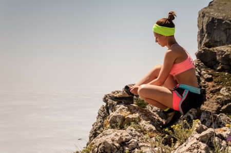 Fitness woman trail runner tying shoelace at mountain top Stock Photo