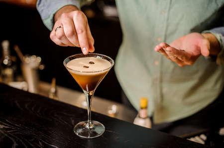 上品なバーテンダーがマティーニ エスプレッソ カクテルを飲む白い泡コーヒー豆一番上のバーのカウンターの上を飾る