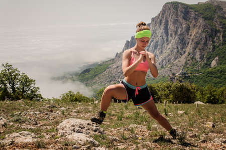 young fitness woman stretching legs on mountain trail
