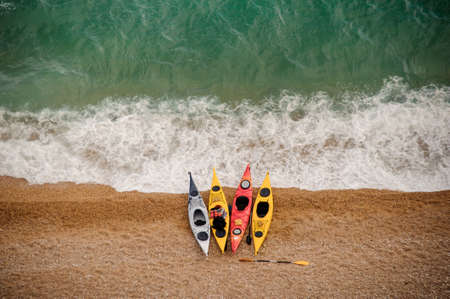 Colorful kayaks on sandy beach. Water sports.