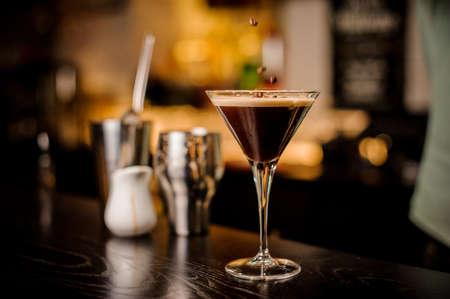 classy bartender garnish martini espresso cocktail drink foam coffee bean on top bar counter Lizenzfreie Bilder