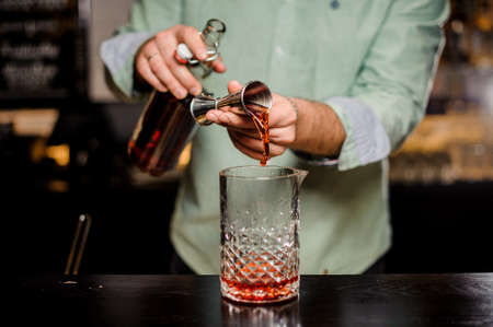 Bartender making alcoholic cocktail in red color, metal jigger and bar environment Lizenzfreie Bilder