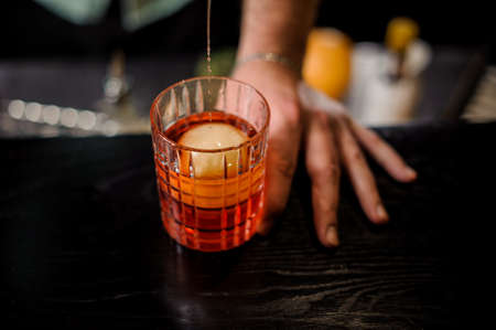 bartender pouring the red cocktail into the glass with ice ball close up