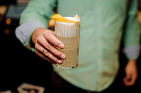 Barmans hands in bar interior making alcohol long cocktail with foam and orange peel. Professional bartender at work in bar. Service industry occupation