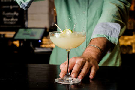 Bartender making white cocktail with lime close up