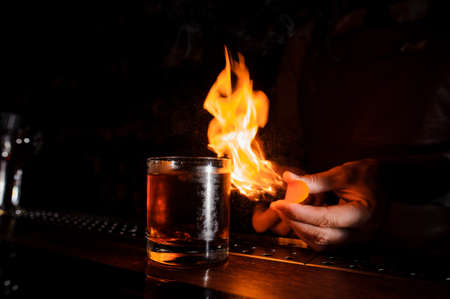 The bartender makes flame above cocktail close up Lizenzfreie Bilder