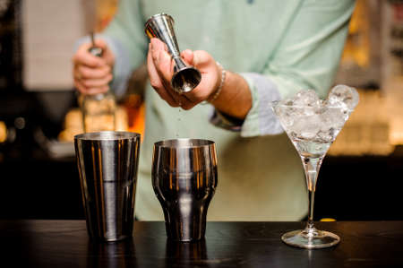 Bartender hands pouring alcoholic drink into a jigger to prepare cocktail close up