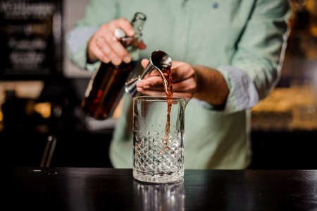 Bartender making alcoholic cocktail in red color, metal jigger and bar environment close up