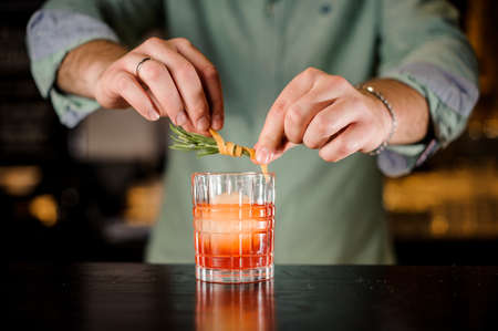 No face bartender decorates red cocktail with orange peel and rosemary