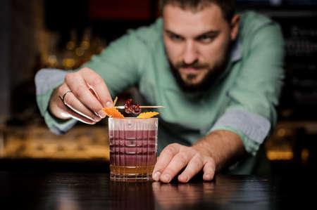 Bartender is decorating whisky sour cocktail with cherry. New York sour Lizenzfreie Bilder