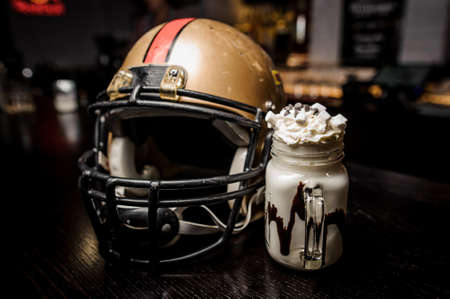 Milk chocolate drink with marshmallow on the background of a football helmet close up