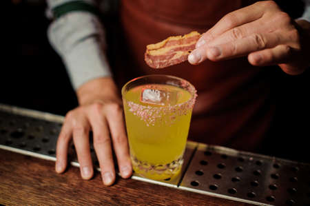 Delicious cocktail based on vodka with bacon and salt close up