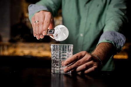 A professional bartender is holding an ice ball. close up Lizenzfreie Bilder