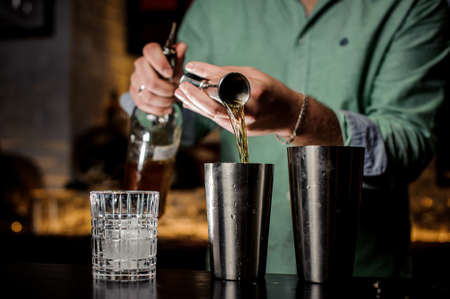 The bartender pours alcohol in a bar. Two shakers, a bottle, a jiger and a glass with ice