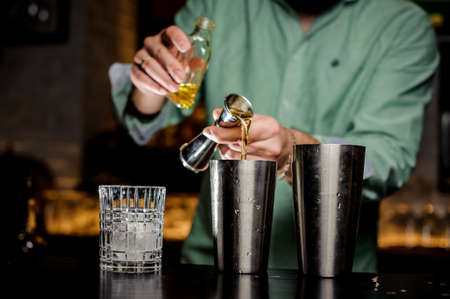 The bartender no face pours alcohol in a bar. Two shakers, a bottle, a jiger and a glass with ice Lizenzfreie Bilder