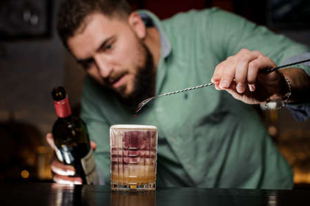 Bartender adds wine to the cocktail. A fascinating moment.