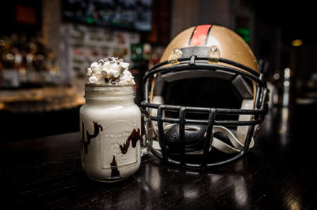Milk chocolate drink with marshmallow on the background of football helmet close up