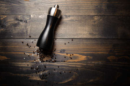 Pepper shaker with papper corn on wooden background. Dark effect style pictures