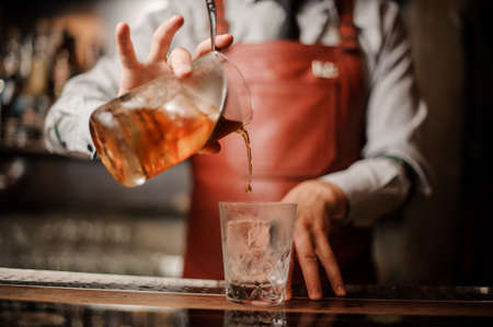 Barmans hands in bar interior making alcohol cocktail. Professional bartender pours a drink with a strainer