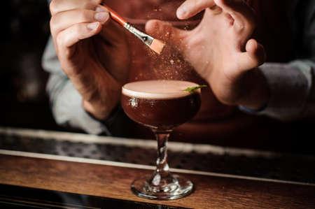 The barman decorates the cocktail with a gold powder. Magic image. No face Lizenzfreie Bilder