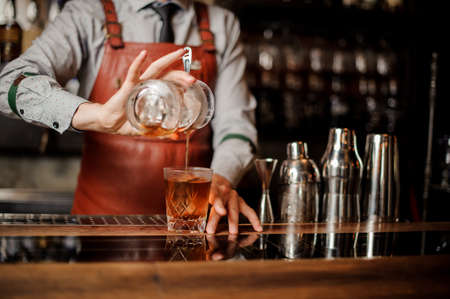 Barman in bar interior making alcohol cocktail. Professional bartender pours a drink with a strainer Lizenzfreie Bilder