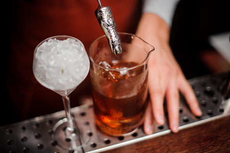 The bartender mixes a cocktail with a bar-spoon in the form of a finger close up
