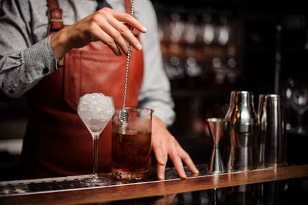 The bartender mixes a cocktail with a bar-spoon in the form of a finger