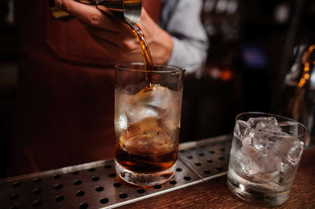 Close up shot of barman hand pouring drink from measuring cup into a cocktail glass filled with ice cubes. Male bartender preparing fresh cocktail.