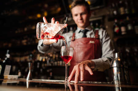 close up of bartender pouring bright red alcohol cocktail into the glass