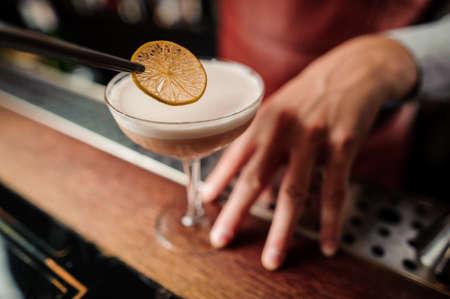 Sicilian sour cocktail in bartenders hands close up Lizenzfreie Bilder