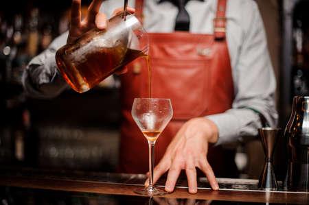 유리에 밝은 빨간색 알코올 칵테일을 붓는 바텐더의 폐쇄