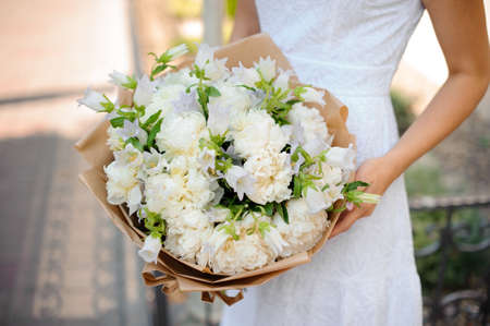 Simple white wedding bouquet in the hands of a woman close up