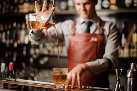 Barman in bar interior making alcohol cocktail. Professional bartender pours a drink with a strainer Stock Photo