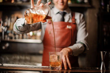 Barman in bar interior making alcohol cocktail. Stock Photo