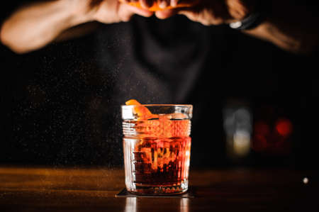 bartender with glass and orange peel preparing cocktail at bar. alcohol drinks, people and luxury concept