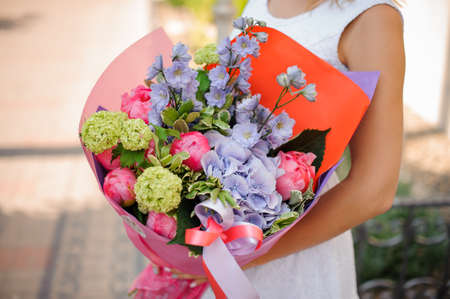 Beautiful colorful wedding bouquet in woman hands on a bright background no face close up Stock Photo