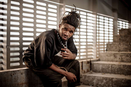 Attractive afro american man with dreadlocks and dressed in black clothes sitting near the window Stock Photo