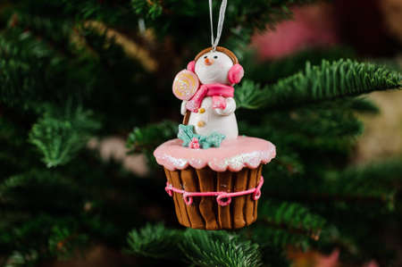 christmastide: Christmas tree decoration toy in the form of sweet cupcake with cute snowman on the top