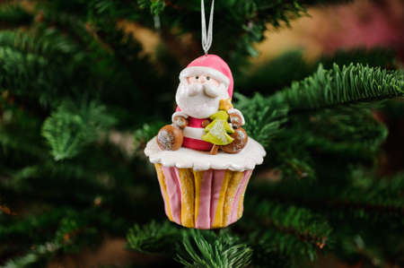 christmastide: Christmas tree decoration toy in a form of sweet cupcake with little Santa Claus on the top