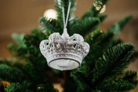christmastide: Silver Christmas tree toy in the form of a little crown on the green background of fir tree Stock Photo