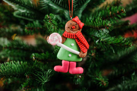 christmastide: Fine Christmas tree toy in the form of cute alive cookie on the green background of fir tree