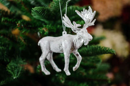 Christmas tree toy in the form of silver moose on the green background of fir tree