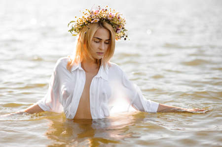 Beautiful and hot blond woman in a white shirt and pretty flower wreath, standing in water