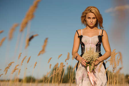 Portrait of a lovely blonde girl in a lingerie standing on the beautiful field with flowers