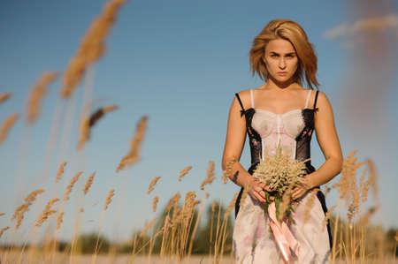 Portret van een mooi blondemeisje in een lingerie die zich op het mooie gebied met bloemen bevinden