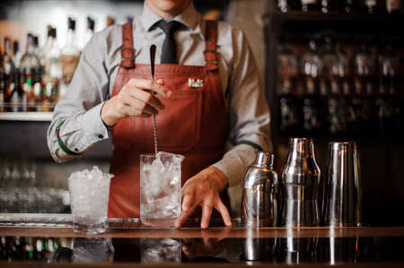 Bartender dressed in grey shirt and apron is making a cocktail with ice on the